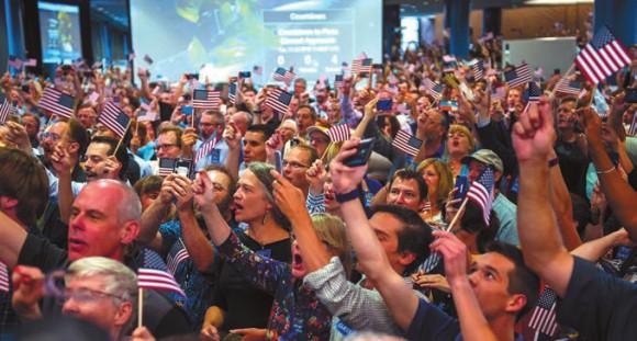 Гости и члены команды New Horizons празднуют момент сближения с Плутоном