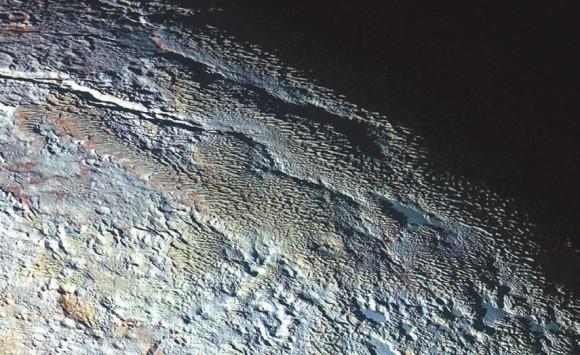 9. На этом комбинированном цветном изображении — производящие весьма странное впечатление округлые и причудливо текстурированные горы, неофициально названные Тартар Дорса. Это что-то вроде шкуры дракона: серо-голубые хребты плюс красноватый материал между ними. Справа вверху — терминатор. Этот фрагмент шириной 530 км сочетает в себе синие, красные и инфракрасные изображения, полученные 14 июля с помощью мультиспектрального «Ральфа» (переданы на Землю 19 сентября). Разрешение — 1,3 км.