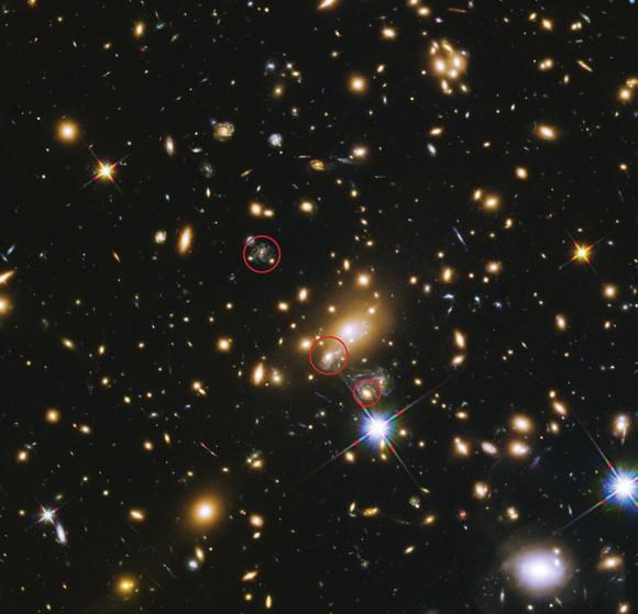 На снимке области скопления галактик MACS J1149.6+2223 кружками обведены три изображения родительской галактики сверхновой Рефсдала. В ноябре 2014 года вспышка проявилась в нижнем изображении. В верхнем изображении ее можно было бы наблюдать много лет назад. В среднем изображении вспышка происходит в данный момент. Фото с сайта www.eso.org
