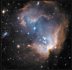Туманность NGC602 в Малом Магеллановом Облаке. Звезды, родившиеся в огромном газово-пылевом облаке, испарили его сердцевину. Слева - еще одно скопление, видимо, постарше, так что вся пыль вокруг уже испарена. Слева внизу сквозь туманность просвечивает аккуратная спиральная галактика.