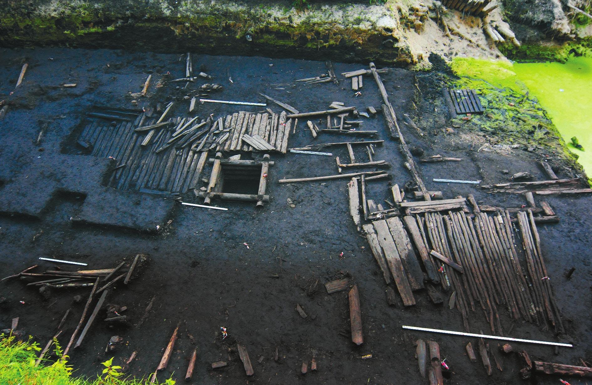 Остатки деревянных настилов середины XIV века и перебивающий их колодец XIX века в северной части раскопа Пятницкий-II