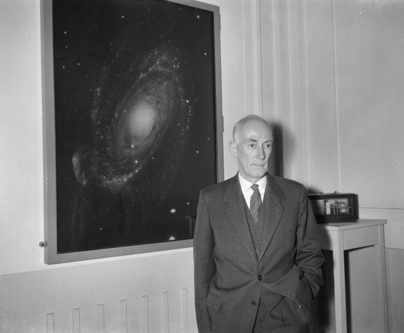 Ян Хендрик Оорт, профессор астрономии в Лейденской обсерватории. Май 1961 года. Позади него - фотография спиральной галактики M81. Национальный архив Нидерландов