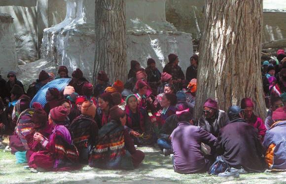 Паломники во дворе в тени деревьев