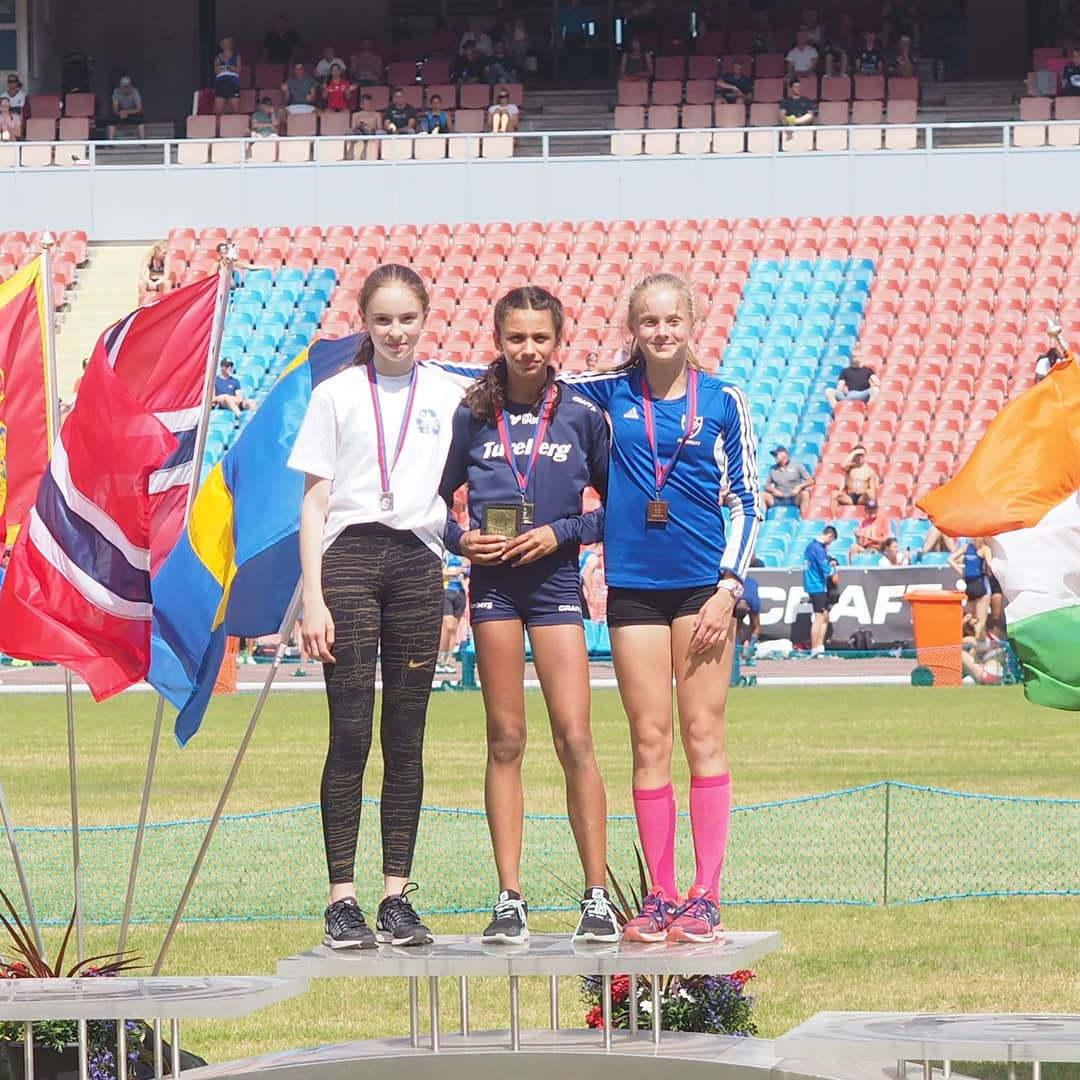 Призеры соревнований в прыжках в длину на фоне «Уллеви»: в центре — чемпионка, Айла Хельберг Хуссейн (прыжок на 5,84 м)