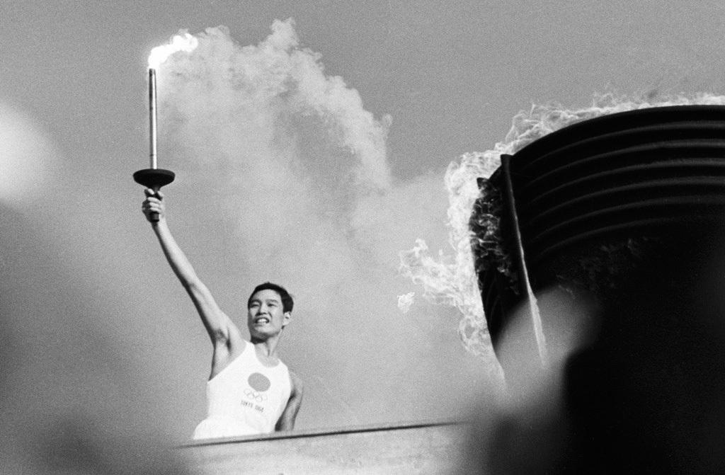 Ёсинори Сакай (Yoshinori Sakai), зажегший на стадионе олимпийский огонь, родился в 60 км от Хиросимы 6 августа 1945 года, в тот самый день, когда на город американцы сбросили атомную бомбу. Он был выбран символом перехода Японии к мирной жизни и обновлению. В 1960 году он как раз стал студентом университета. В 1966 году на Азиатских играх в Бангкоке он завоевал золотую медаль в эстафете. Затем стал журналистом, освещавшим темы спорта. Умер 10 сентября 2014 года