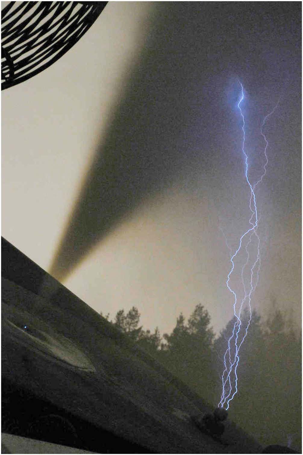 Фото в видимом диапазоне (выдержка 5 с) отрицательно заряженного аэрозольного облака (наклонная темная струя) и четырех восходящих положительных разрядов длиной около 1,5 м, которые поднимаются с заземленного шарика. Внутри облака не видно светящихся образований (из указанной статьи)